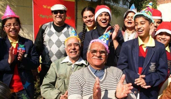 83343-school-children-celebrating-christmas-with-senior-citizens-at-a.jpg
